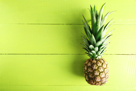 Ripe pineapple on a green wooden background Stock Photo