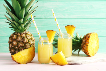 Bottles of pineapple juice on a pink wooden table Stockfoto