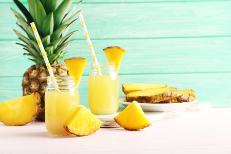 pineapple: Bottles of pineapple juice on a pink wooden table Stock Photo