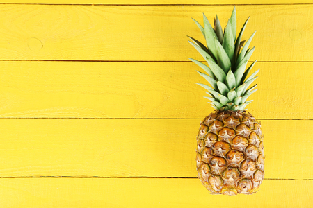 Ripe pineapple on a yellow wooden background Foto de archivo