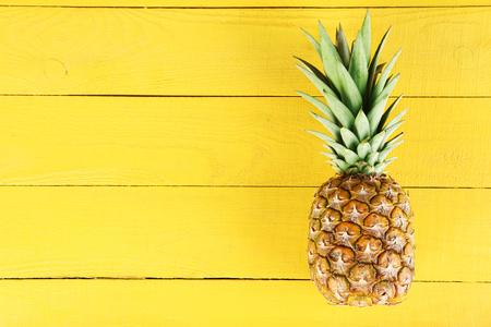 lifestyle: Reife Ananas auf einem gelben Holzuntergrund