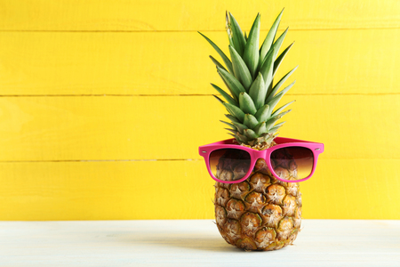 single object: Ripe pineapple with sunglasses on a white wooden table
