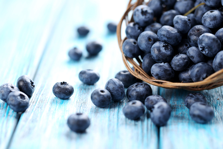 Smaczne jagody w koszu na niebieskim drewnianym stole