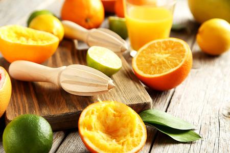 lemon lime: Wooden juicer and orange on a wooden table