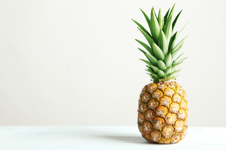 wooden boards: Ripe pineapple on a white wooden table