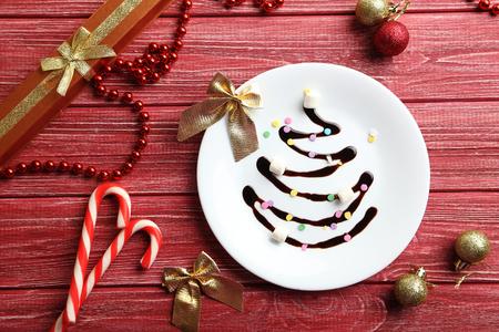 cioccolato natale: Cioccolato di Natale abete sul piatto bianco su tavola di legno rosso Archivio Fotografico
