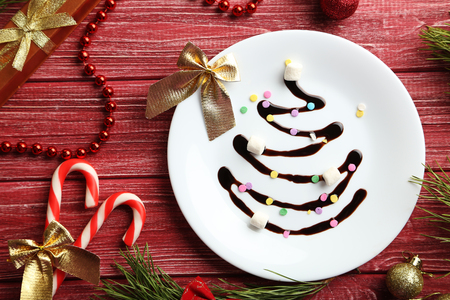 firtree: Chocolate christmas fir-tree on white plate on red wooden table Stock Photo