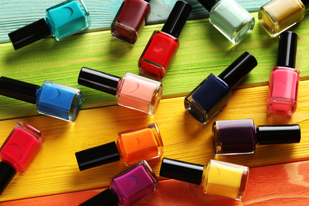 Bottles of nail polish on a colorful wooden table Stockfoto