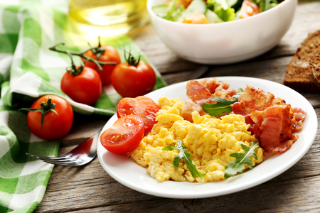eggs and bacon: Scrambled eggs with bacon and vegetables on a grey wooden table