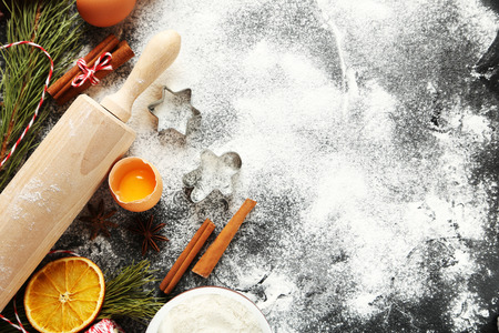christmas food: Christmas tree branch with dried oranges, cinnamon, eggs, flour and anise star on wooden table