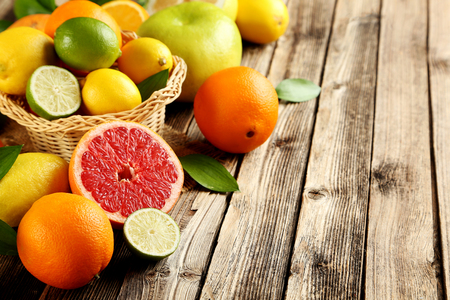 Citrus fruits on a brown wooden table Imagens