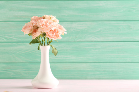 Bouquet of beautiful roses on a pink wooden table Foto de archivo