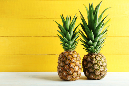 Ripe pineapples on a white wooden table Imagens - 53496712