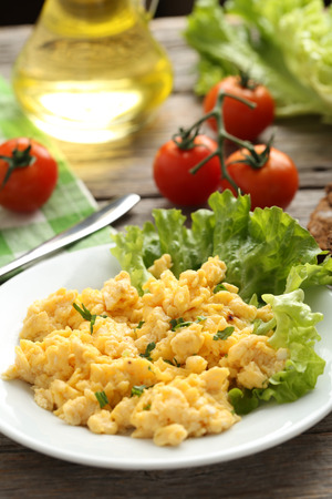 omlet: Scrambled eggs with vegetables on a grey wooden table