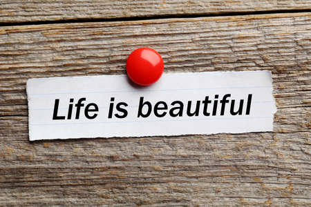 underlying: Sheet of paper on grey wooden background, life is beautiful