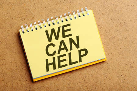 can we help: Notebook on the brown wooden background, we can help