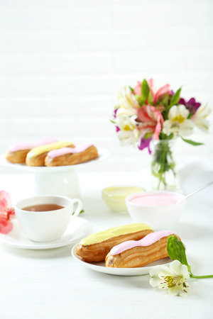 glaze: Eclairs with glaze on a white wooden table