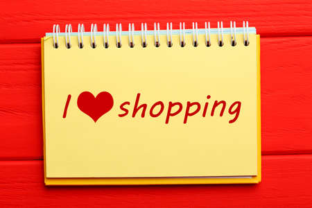 underlying: Notebook on a red wooden background, i love shopping