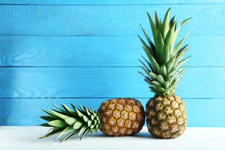 pineapple juice: Ripe pineapples on a white wooden table
