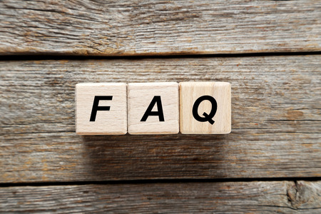 faq: Wooden toy cubes on a grey wooden table