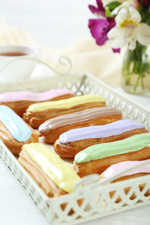 profiterole: Eclairs with glaze on a white wooden table