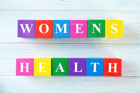 Women's health: Colorful wooden toy cubes on a blue wooden background