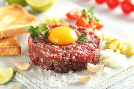 Beef tartare with egg yolk on a blue wooden table 스톡 콘텐츠