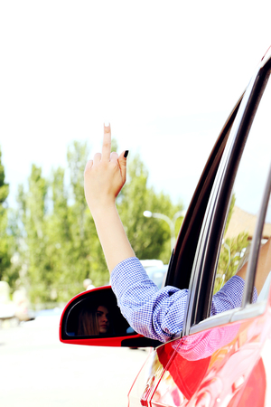 Angry woman driver showing middle finger Stock Photo