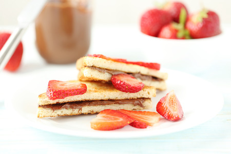 nutella: French toasts with chocolate and strawberry on wooden table