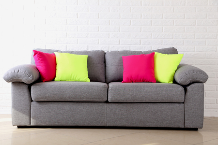 case sheet: Colorful pillows on grey sofa on a brick wall background