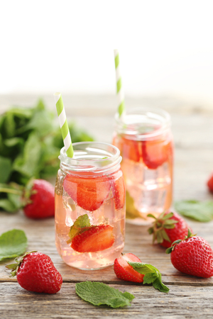 Fresh strawberry drink in bottle on wooden table
