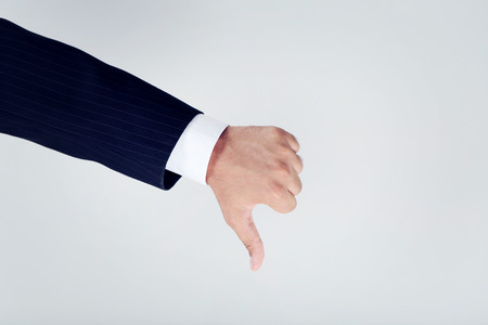 thumbs down: Businessman gesturing thumbs down on grey background