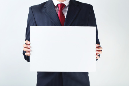 hoja en blanco: Businessman holding blank sheet of paper in his hands Foto de archivo