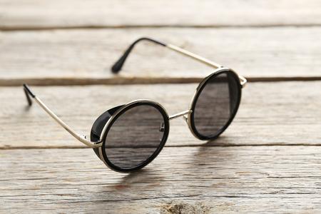Black sunglasses on a grey wooden table Reklamní fotografie