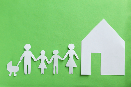 Happy paper family on green background Stock Photo