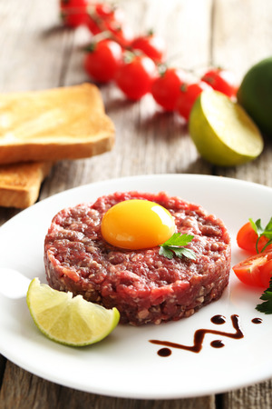 Beef tartare with egg yolk on a grey wooden table Stock Photo