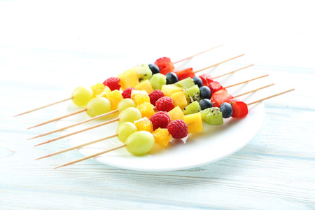brochetas de frutas: La fruta fresca en los pinchos en una mesa de madera blanca Foto de archivo
