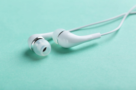 White headphones on a mint paper background