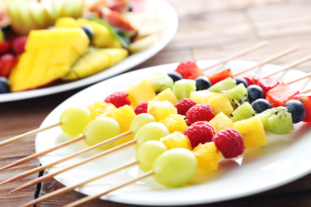 brochetas de frutas: La fruta fresca en los pinchos en una mesa de madera marrón Foto de archivo