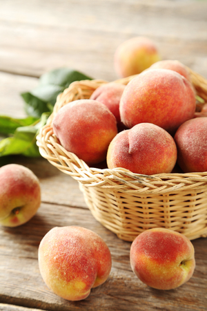 apricots: Sweet peach fruit in basket on grey wooden table Stock Photo
