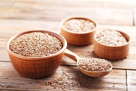 brown flax: Brown flax seeds on a wooden table Stock Photo