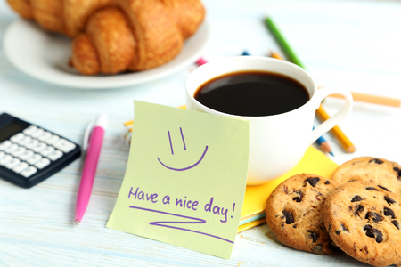 Piece of note paper with cup of coffee and cookies on blue wooden background