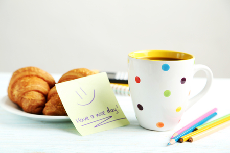 Piece of note paper with cup of coffee and croissant on blue wooden background