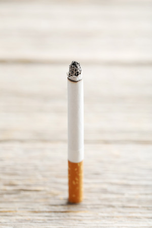 Cigarette with ash on grey wooden table