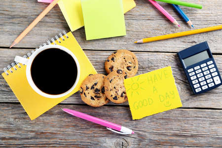 Piece of note paper with cup of coffee and cookies on grey wooden background Stock Photo
