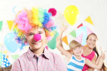 Little boy clown and girls having fun at birthday party Stock Photo