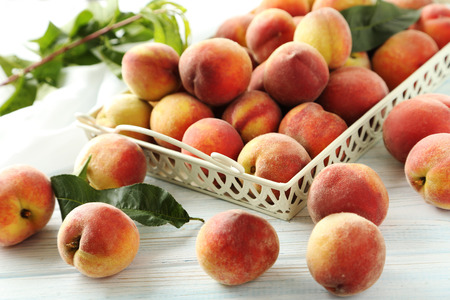 Sweet peach fruit in tray on white wooden table