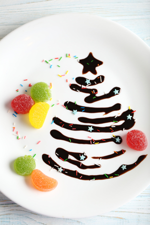 cioccolato natale: Chocolate christmas fir-tree on white plate on blue wooden table
