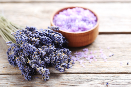 Bunch of lavender flowers with sea salt in bowl on grey wooden table