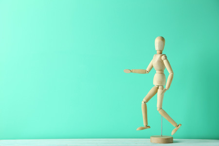 proportions of man: Wooden figure on a green wooden table Stock Photo